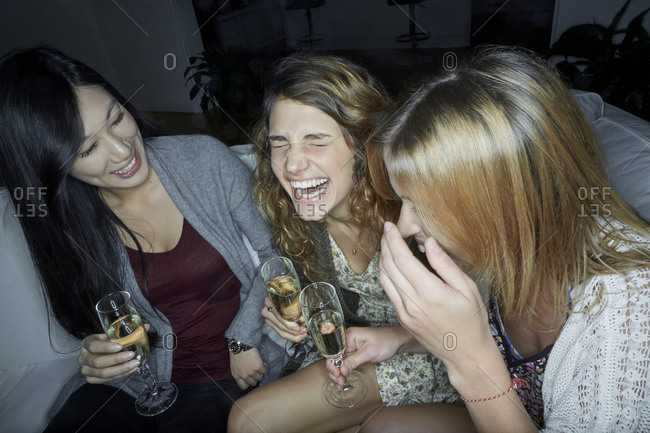 Three happy women sitting on couch drinking champagne