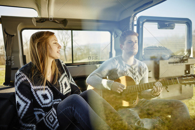 Young couple making music inside car