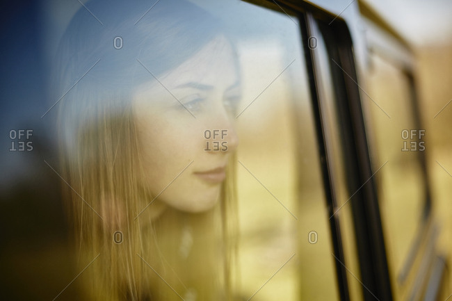 Young woman inside car looking out of window