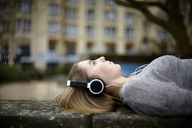 Relaxed young woman wearing headphones lying down