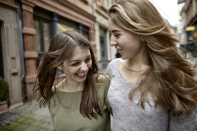 Two happy young women strolling in the city