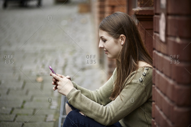 Young woman sitting on doorstep checking cell phone