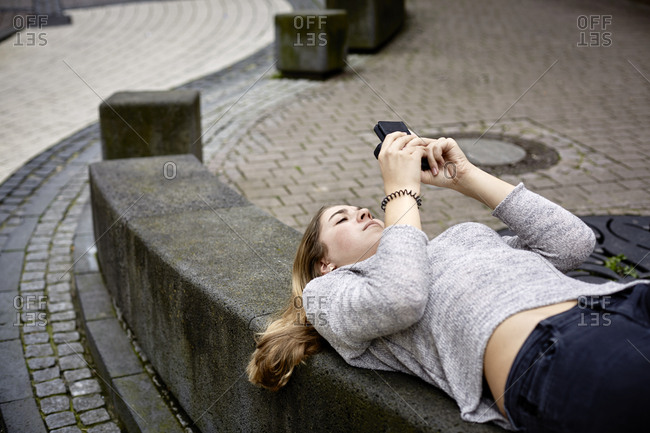 Young woman lying on wall checking cell phone
