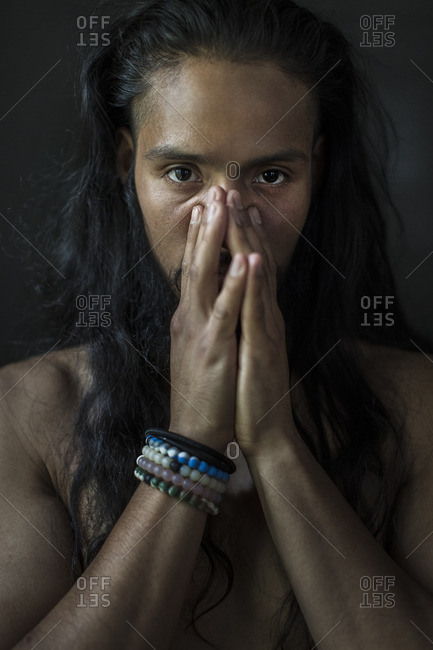 Portrait of young man with hands clasped over face against black background