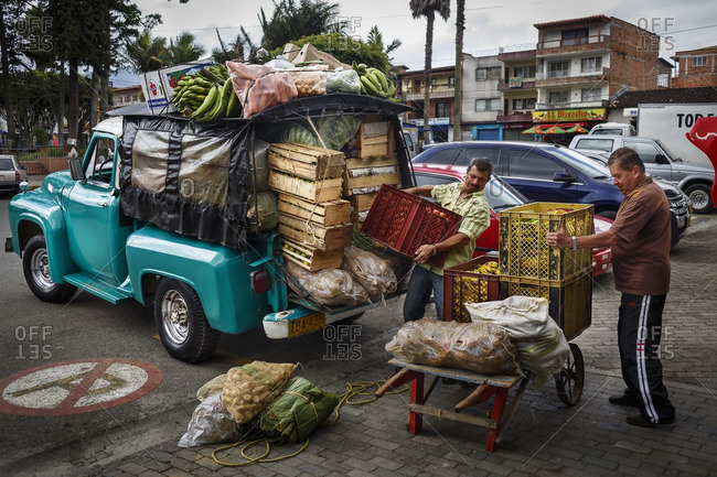 Carmen de Viboral, Colombia - January 3, 2013: Two men unloading food from a truck in a parking lot