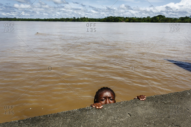 Colombia - June 26, 2014: Girl holding from a wall near the Atrato river