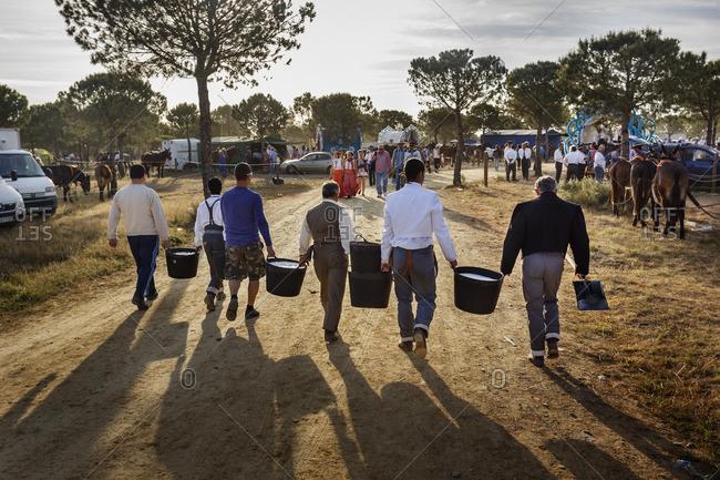 Andalucia, Spain - May 25, 2012: Men carrying buckets of ice in El Rocio pilgrimage