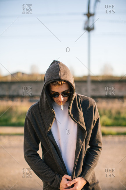 Portrait of young man with his head down smoking a cigarette