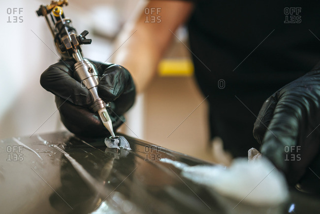 Close-up of tattoo artist's hands with tattoo machine picking up ink