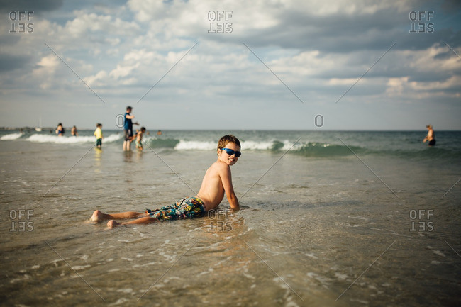Boy lying down in shallow waves on a beach