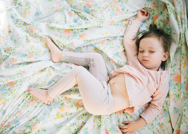 Toddler girl napping on floral sheets