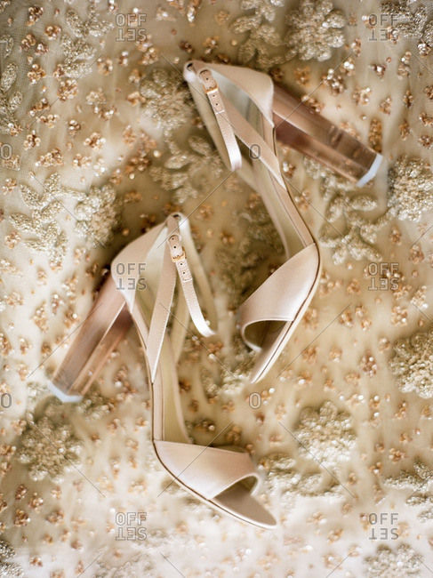 Cream-colored open-toe sandals on the skirt of a beaded gown