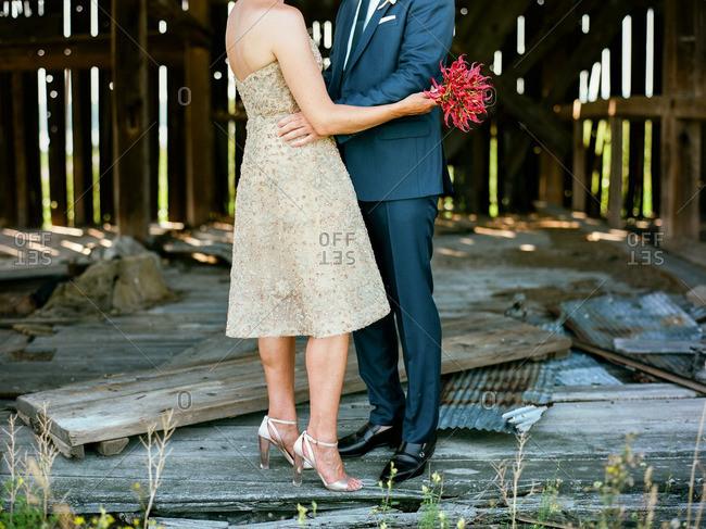 Couple in formalwear embracing in a rustic barn