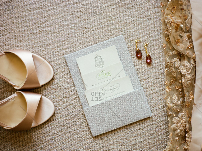 Sandals, earrings and the hem of a dress with an invitation to a special event