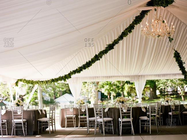 Tables set under a billowy white open-air canopy for a special event