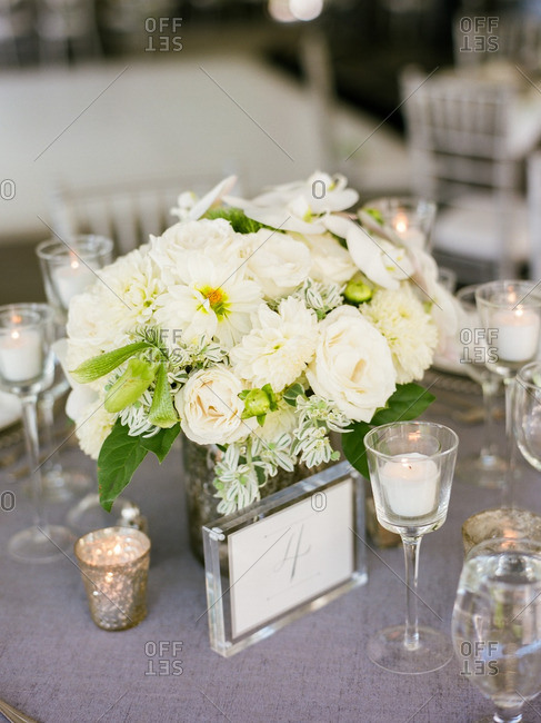 Centerpiece bouquet with a table number and votive candles at a reception