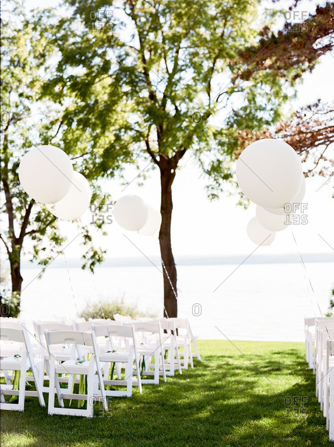 Rows of guest chairs on a waterfront lawn at an outdoor wedding