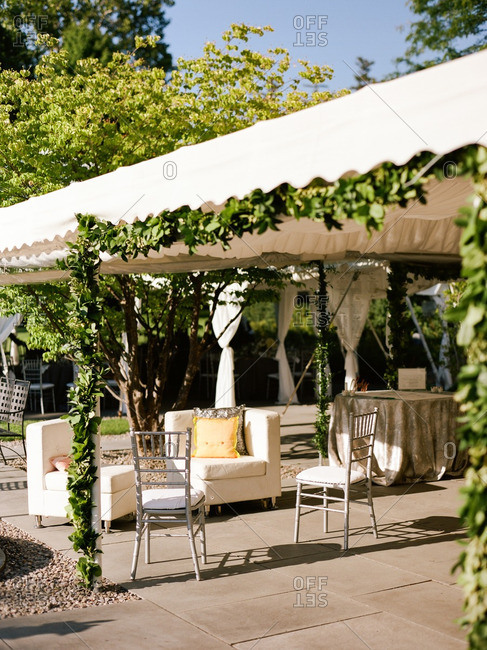 Reception seating area under a white tent with green vines