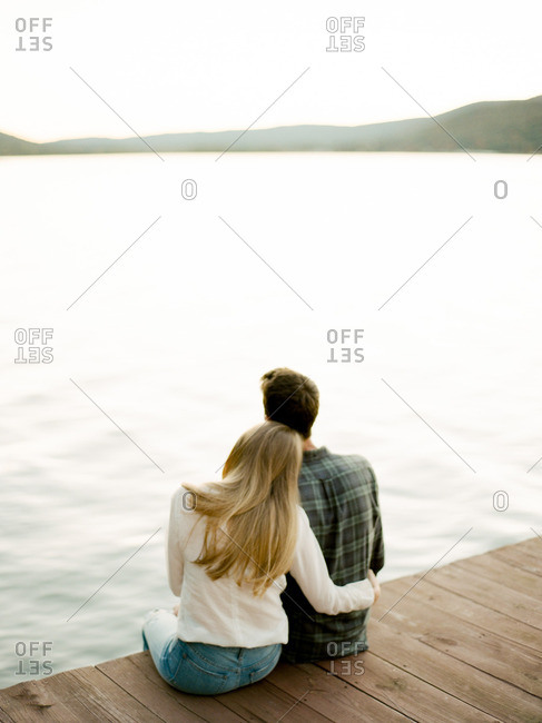 Couple sitting together on a dock looking out over a lake