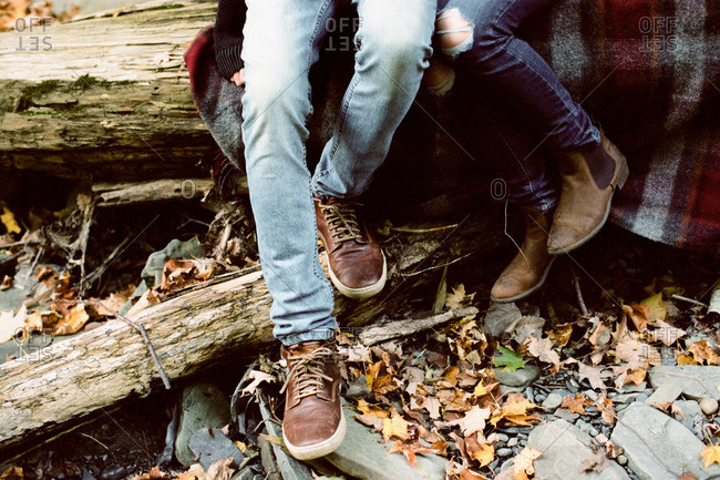Couple curled up on a flannel blanket on a fallen log