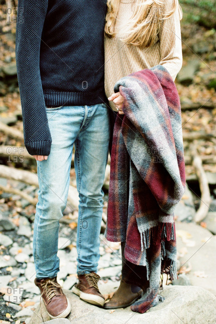 Engaged couple standing together on a rock holding a flannel blanket