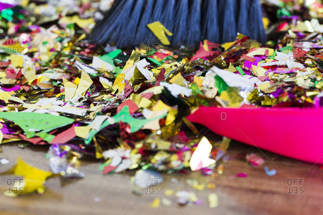 Broom sweeping up colorful pieces of metallic confetti