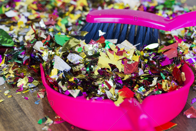 Brush sweeping colorful pieces of confetti into a dustpan
