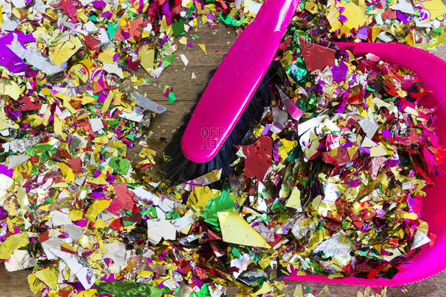 Colorful metallic confetti being swept into a dustpan