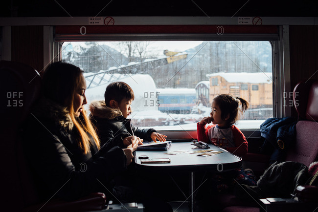 Family of three sitting together at a table on a train