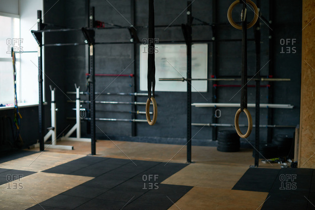 Large empty gym equipped with mats, gymnastic rings and bars of different sizes