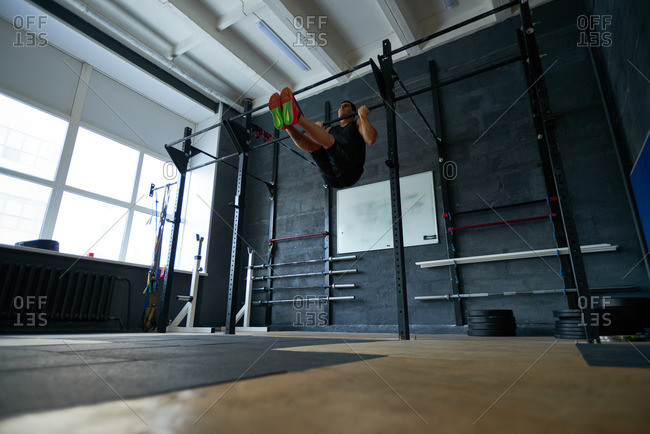 Athletic man in sportswear building muscles by doing pull-ups on bar alone in roomy gym
