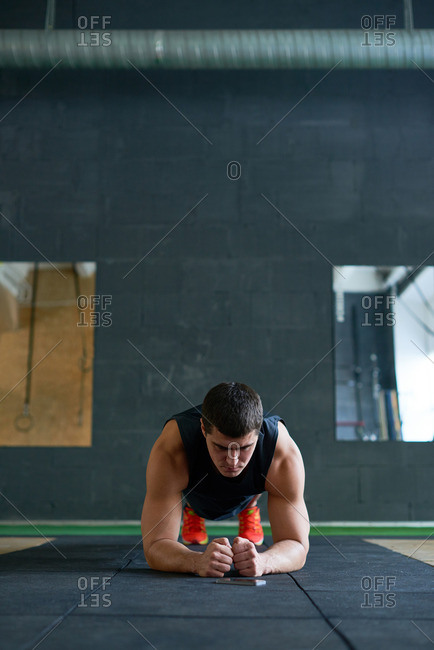 Young muscular black-haired sportsman standing in plank position on mat while training in sport club, his biceps tightened