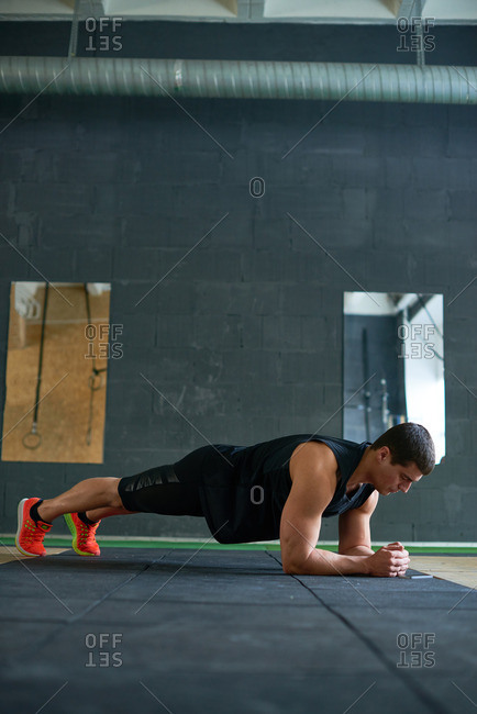 Young black-haired male athlete building muscles while doing planking exercise on dark gray mat in gym