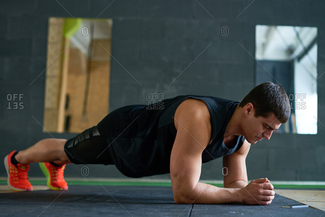 Dark-haired muscular athlete in sportswear strengthening his abs and will by standing in plank position on mat, eyes closed and biceps tightened