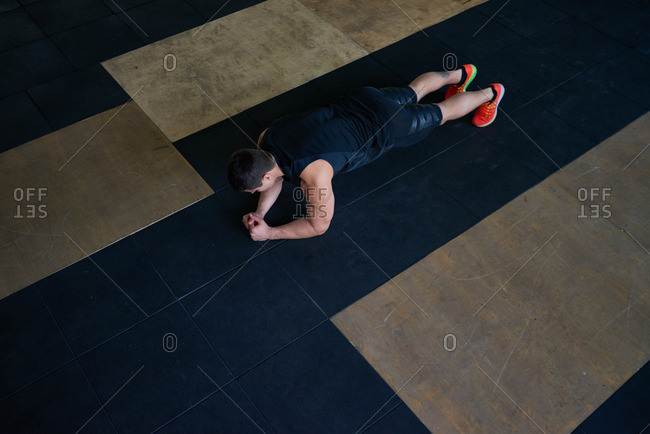 Young athlete in sportswear standing in plank on black mat with his biceps tightened