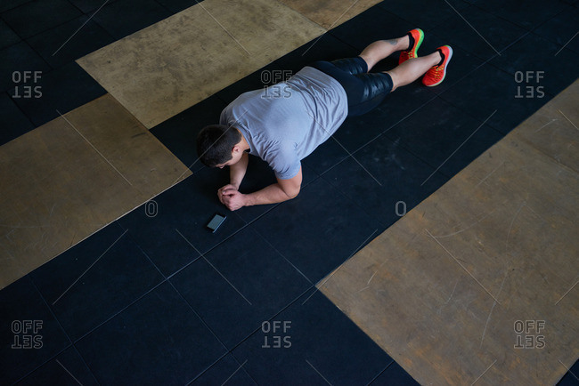 Dark-haired athlete in active wear holding plank on mat with noted time on his smartphone, high angle view