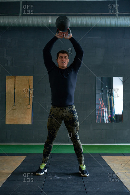 Young muscular athlete in sportswear standing on mat, holding heavy kettlebell overhead and looking at camera