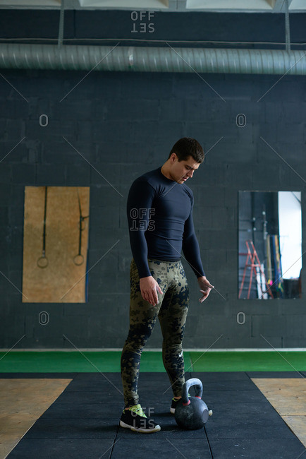 Black-haired muscular sportsman in active wear standing on mat and getting ready to lift heavy kettlebell