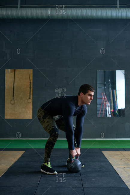 Young muscular gym instructor in sportswear standing in quarter squat position and getting ready to lift heavy kettlebell