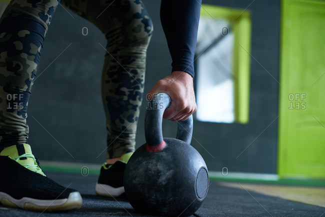 Close-up view of male athlete in military leggings gripping handle of kettlebell with one hand