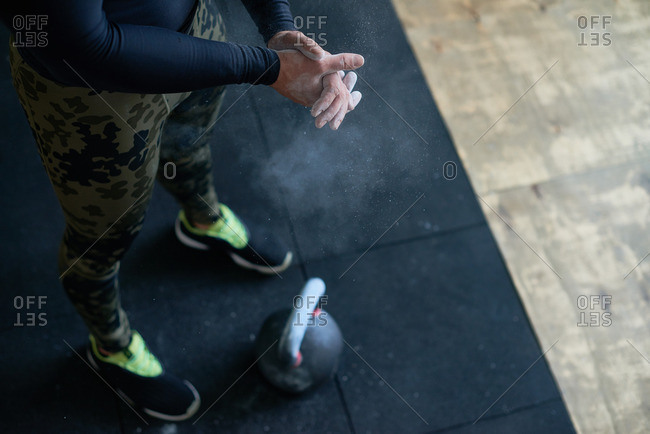 Close-up view of male athlete in military tight pants coating his hands with chalk before lifting kettlebell