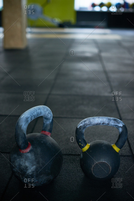 Two kettlebells of different sizes slightly covered with chalk lying on dark weightlifting rubber mat