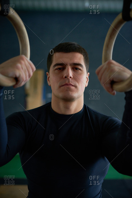 Confident professional gym trainer in sportswear holding gymnastic rings and looking at camera with serious face expression