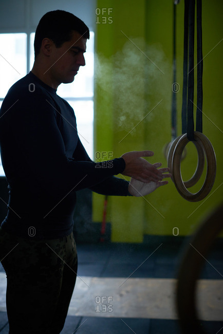 Concentrated professional male athlete chalking his hands before doing exercises with steady rings