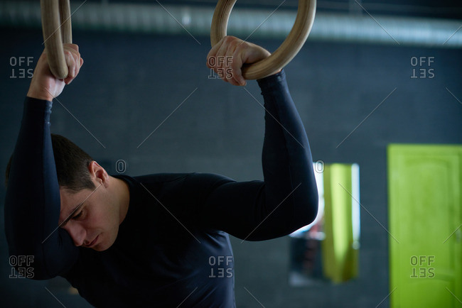 Tired young athlete standing with head dropped on his arm, holding gymnastic rings and looking down unhappily