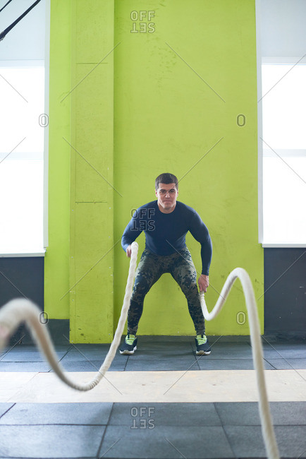 Concentrated muscular athlete in sportswear doing effective exercise by making waves with training ropes standing on mat in gym