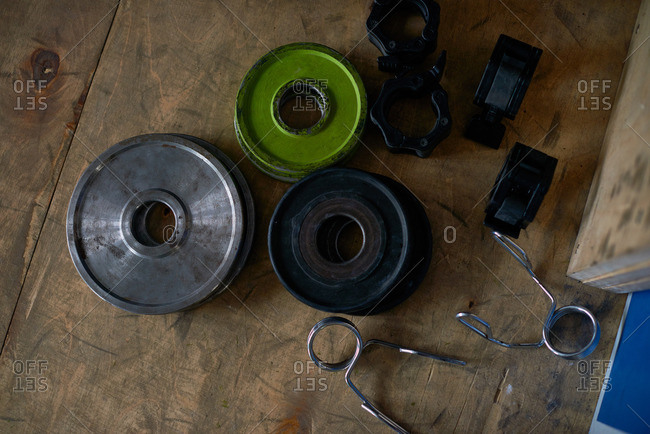 Top view of lock-jaw, spring barbell collars and weight plates lying on wooden background