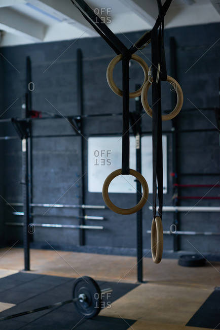 Professional wooden steady rings with straps hanging in well-equipped weightlifting gym