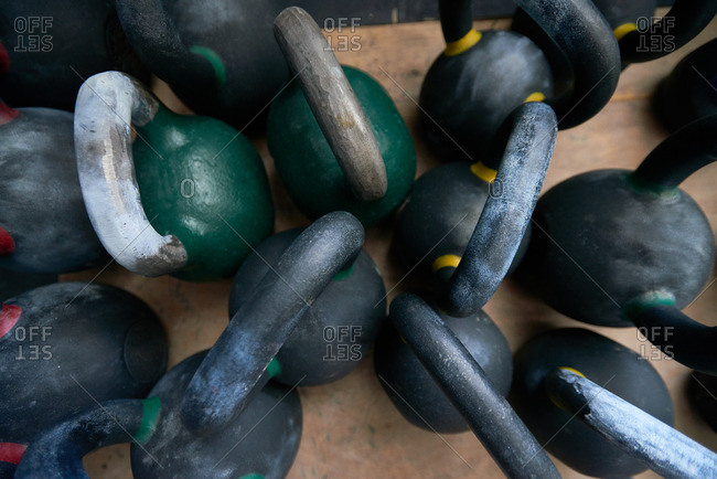 Plenty of color-coded cast iron kettlebells lying on wooden floor in gym, close-up top