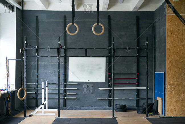 Modern -training gym equipped with bars, weight plates, gymnastic rings, skipping-ropes and rubber mats